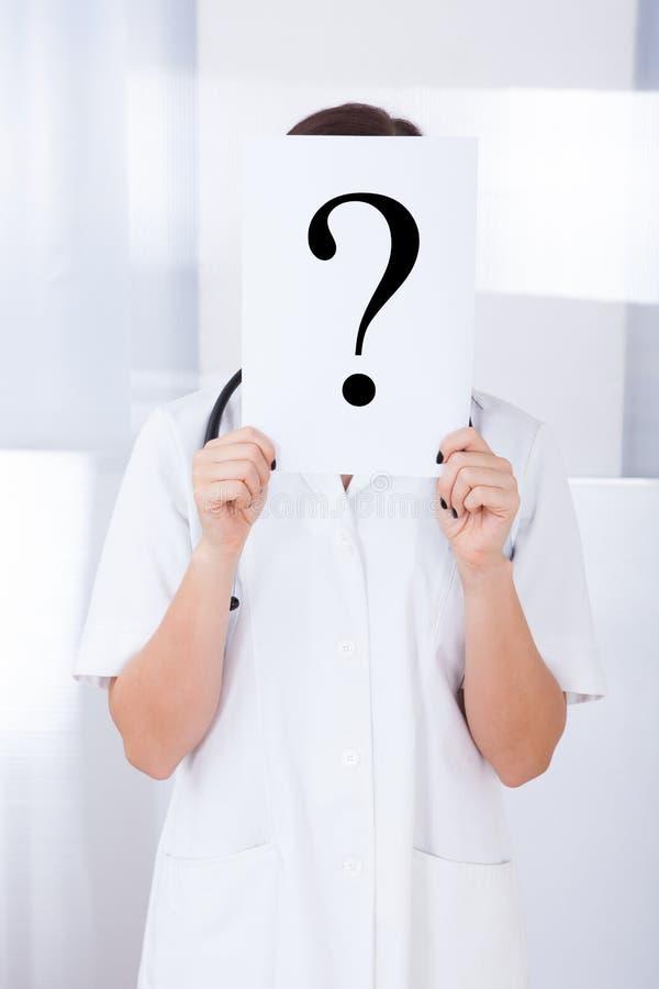 O doutor que guarda o ponto de interrogação assina dentro o hospital fotografia de stock