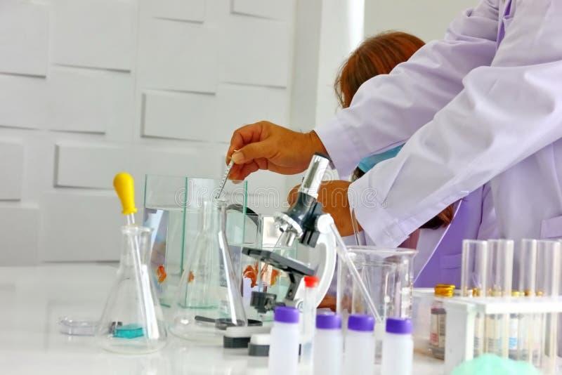 O doutor, reseacher está misturando a droga nova, equipamento de laboratório do wirh do produto no quarto desinfetado fotos de stock