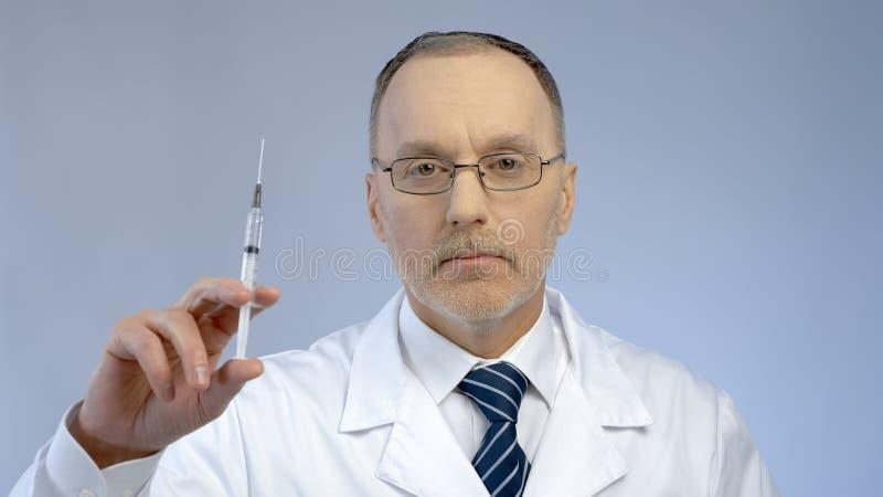 O doutor sério que guarda a seringa, apronta-se para fazer a injeção vacinal, epidemia da gripe imagens de stock royalty free