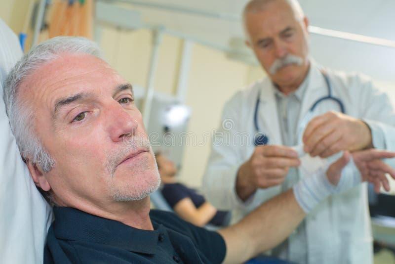 O doutor superior que põe a atadura sobre mais velho equipa o braço foto de stock royalty free
