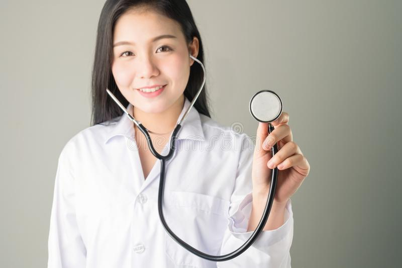 O doutor usa o estetoscópio para alcançar acima e levantar imagem de stock