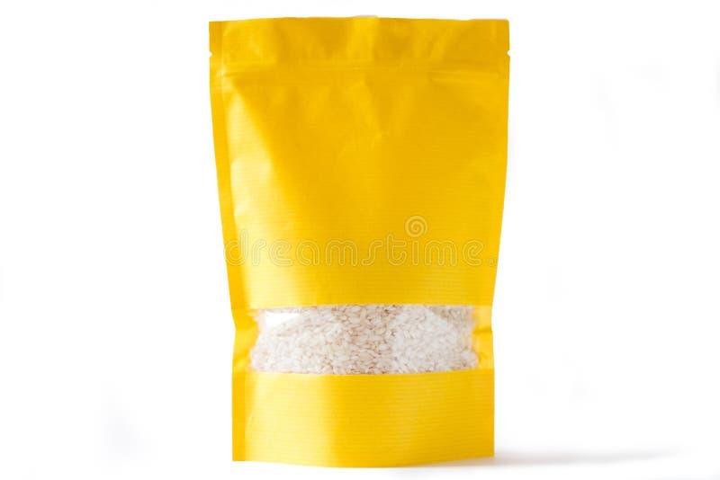 O doypack amarelo do papel levanta-se o bio malote com o zíper da janela no fundo branco enchido com o arroz imagem de stock royalty free