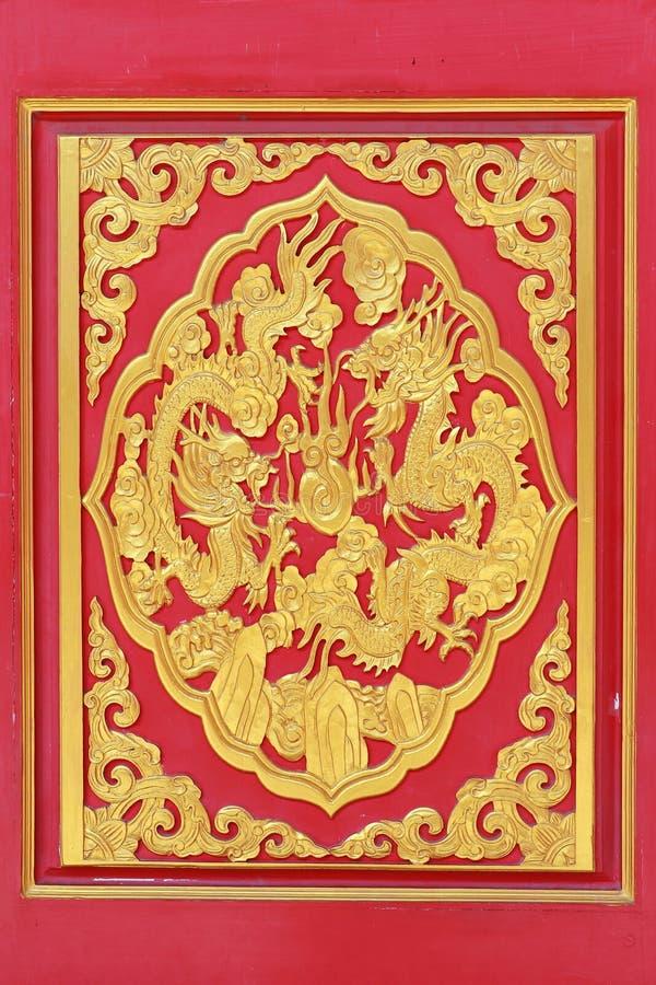 O dragão dourado decorado na madeira cinzelou na porta vermelha, janela vermelha imagens de stock royalty free