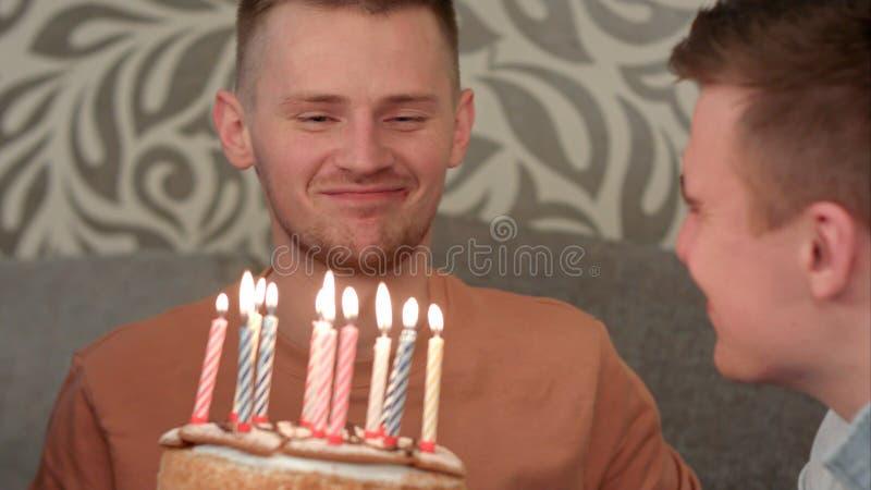 O dreamsabout considerável do menino seu desejo e funde para fora velas no bolo de aniversário e bebe o juce alaranjado fotografia de stock royalty free