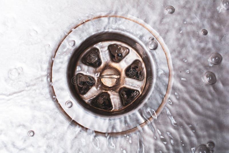 O dreno sujo brilhante de uma banca da cozinha com água de fluxo, parte superior vê para baixo foto de stock