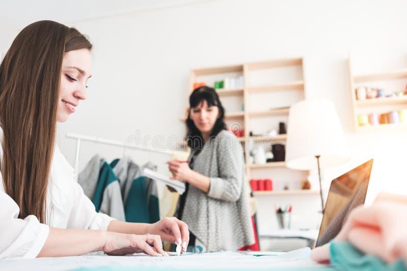 O dressmaster das jovens mulheres cria a roupa do novo conceito com o portátil contemporâneo na sala de exposições da costura Wor fotos de stock