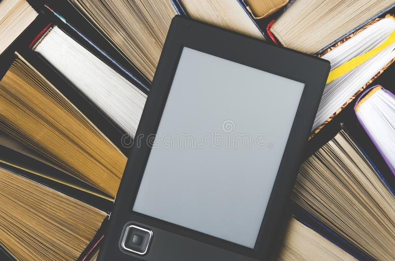 O eBook com uma tela branca encontra-se nos livros multi-coloridos abertos que se encontram em um fundo escuro, close-up fotos de stock
