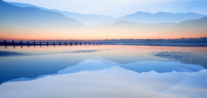 O efeito da técnica da exposição dobro das montanhas e o nascer do sol encalham fotos de stock royalty free