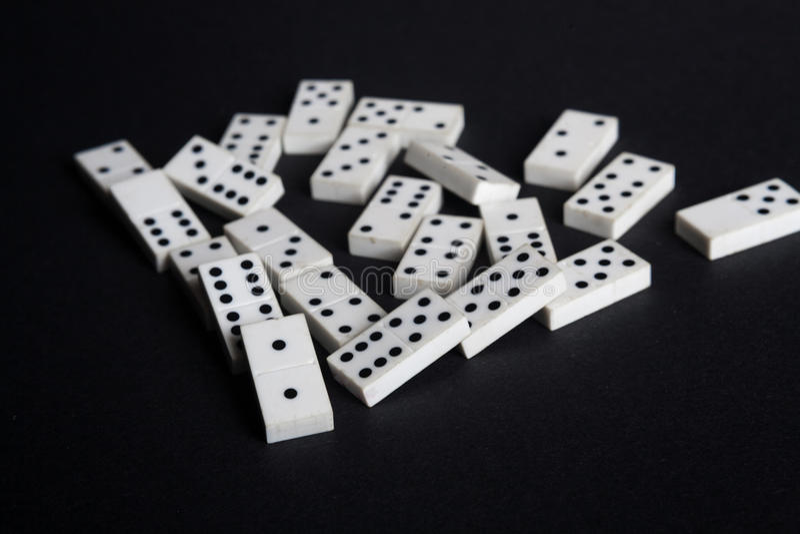 O efeito de dominó caído dos dominós perde o fundo do preto do conceito da falha foto de stock royalty free