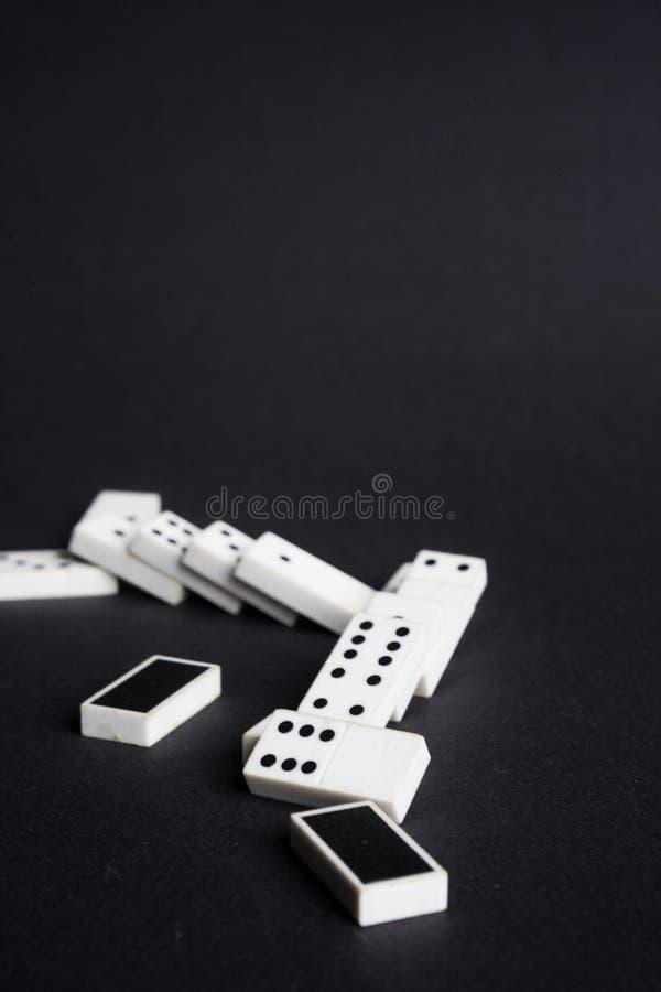 O efeito de dominó caído dos dominós perde o fundo do preto do conceito da falha imagem de stock royalty free