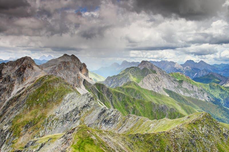 O eixo da chuva bate o cume principal Itália Áustria dos cumes zigzagging Carnic fotografia de stock