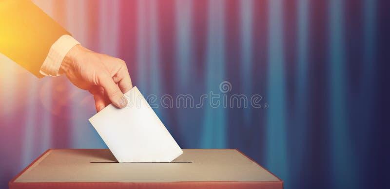 O eleitor guarda a superfície acima disponivel do azul da cédula do voto do envelope Conceito da democracia da liberdade imagens de stock