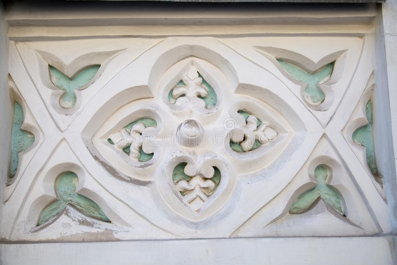 O elemento da terminação de um emplastro da fachada O retângulo dentro de quatro flores nas bordas das pétalas é branco alguns el fotografia de stock