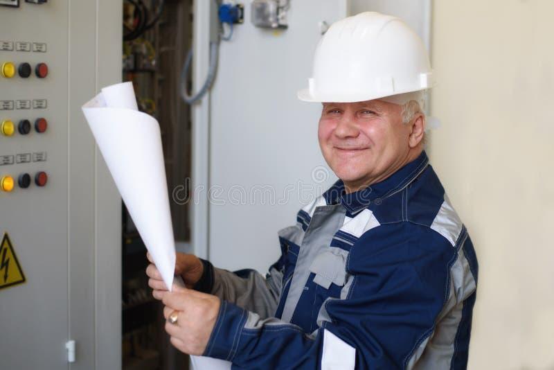 O eletricista do contramestre examina o esboço de trabalho ao lado do painel Energia e seguran?a el?trica fotos de stock