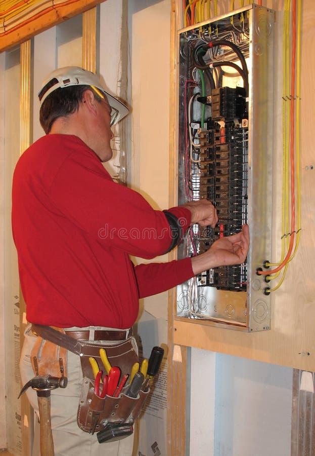 O eletricista faz conexões na caixa do painel fotografia de stock royalty free