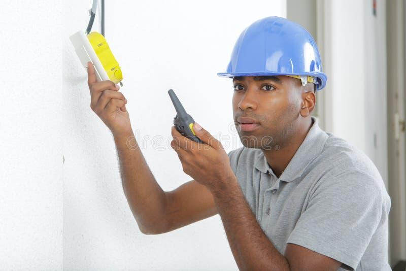 O eletricista instala o soquete emparelhado na parede fotos de stock