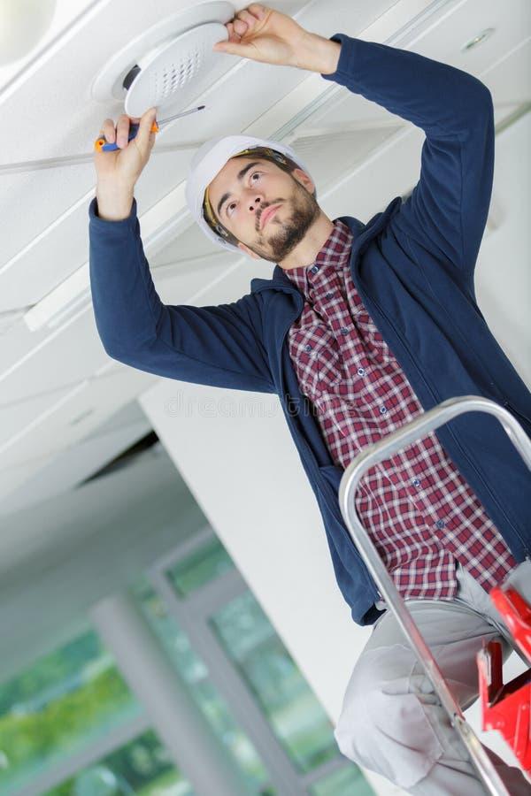O eletricista monta a lâmpada do halogênio na luz de teto na sala fotografia de stock royalty free