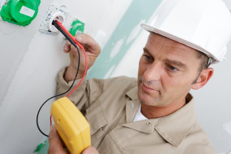 O eletricista monta o soquete de parede bipolar padrão foto de stock