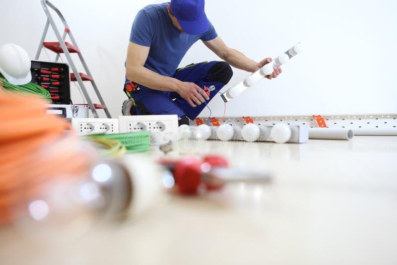 O eletricista no trabalho com pinças cortou o cabo elétrico, instala lâmpadas em casa, circuitos elétricos, fiação elétrica foto de stock