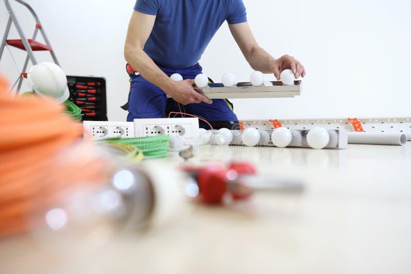 O eletricista no trabalho que instala a lâmpada, com bulbo à disposição, instala circuitos elétricos, fiação elétrica fotos de stock royalty free