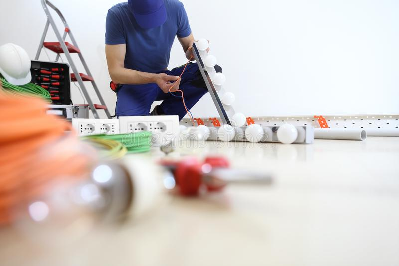 O eletricista no trabalho que instala a lâmpada, verifica o cabo, instala circuitos elétricos, fiação elétrica fotos de stock