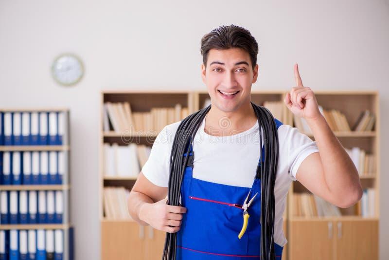 O eletricista novo com o cabo que trabalha no escritório fotografia de stock royalty free