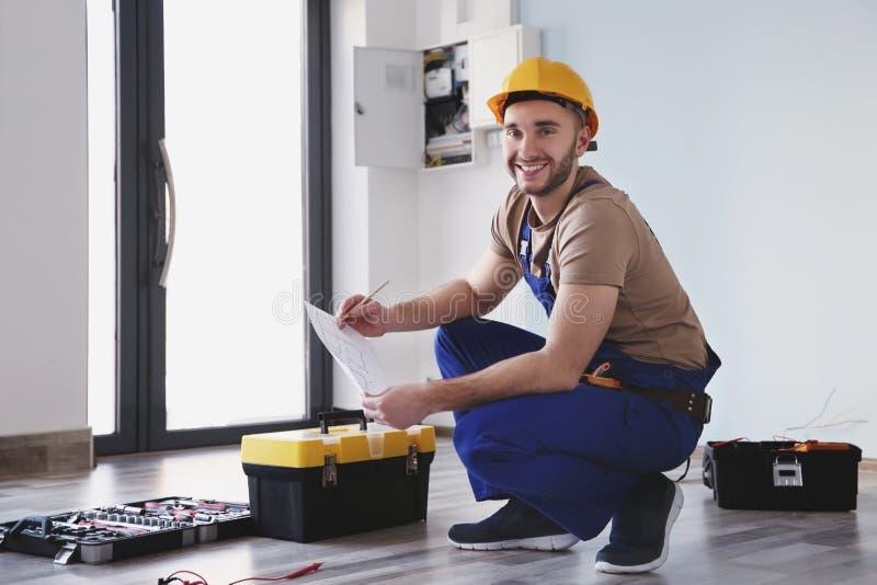O eletricista novo que verifica desenhos aproxima caixas de ferramentas imagens de stock