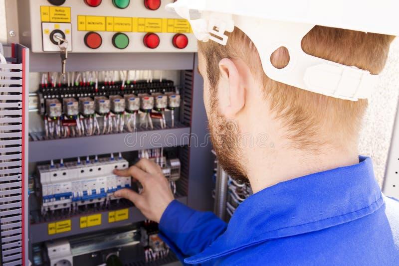 O eletricista que trabalha no capacete branco comuta o interruptor no armário bonde Os trabalhos do coordenador imagens de stock