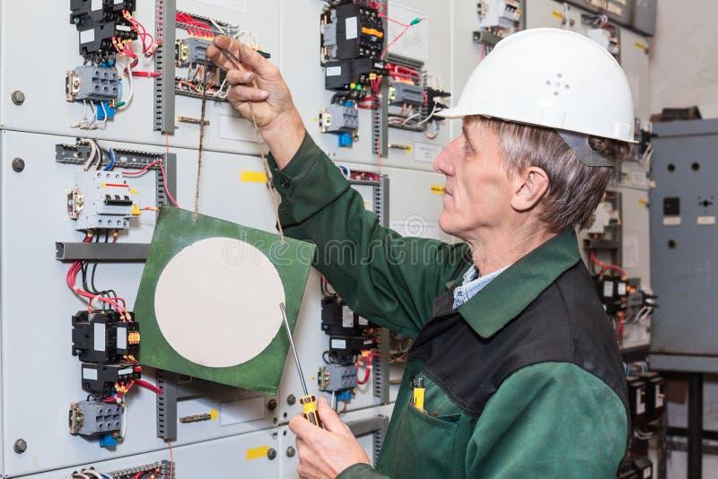 O eletricista superior com uma chave de fenda ajusta um sinal no protetor bonde, placa de identificação clara foto de stock