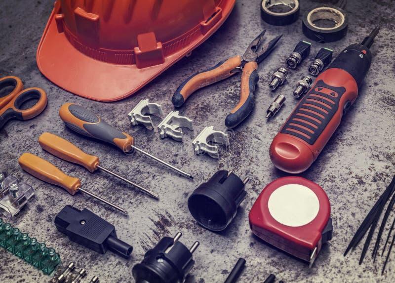 O eletricista utiliza ferramentas o fundo foto de stock