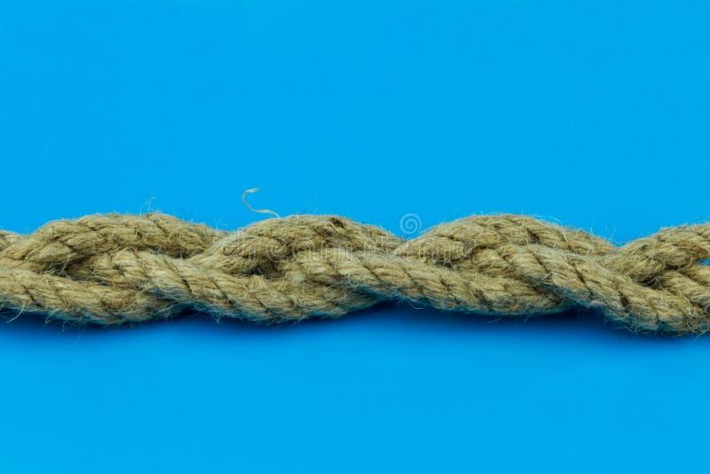 O emperramento da corda do coco de três partes em um fundo azul é horizontal imagem de stock royalty free