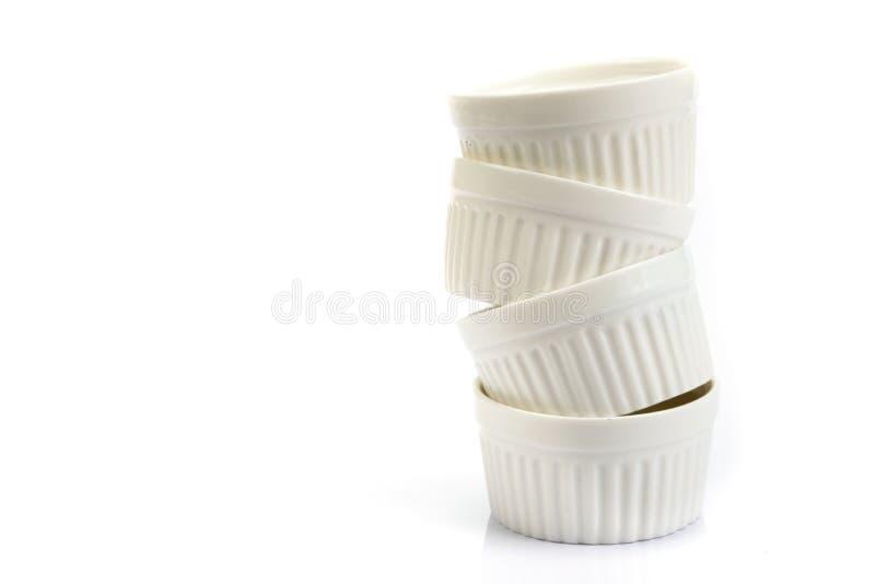 o empilhamento do copo branco pequeno da padaria no fundo branco imagens de stock