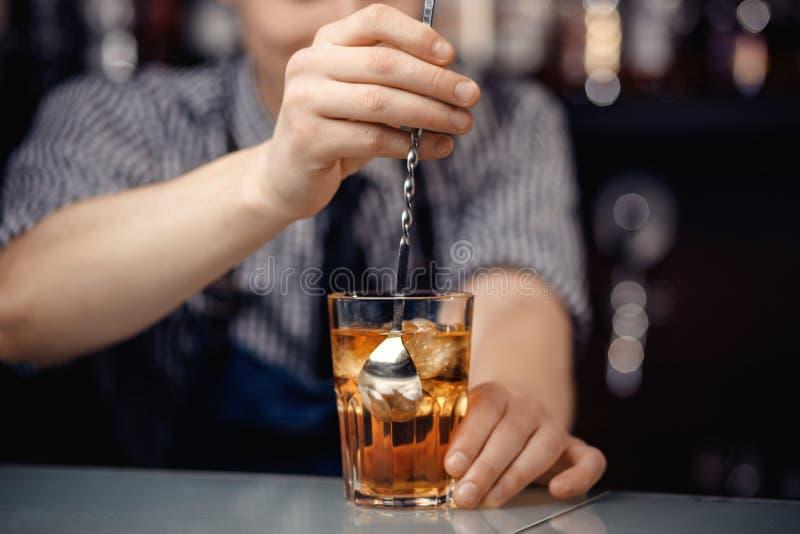 O empregado de bar agita o cocktail com gelo na colher longa de vidro fotografia de stock royalty free
