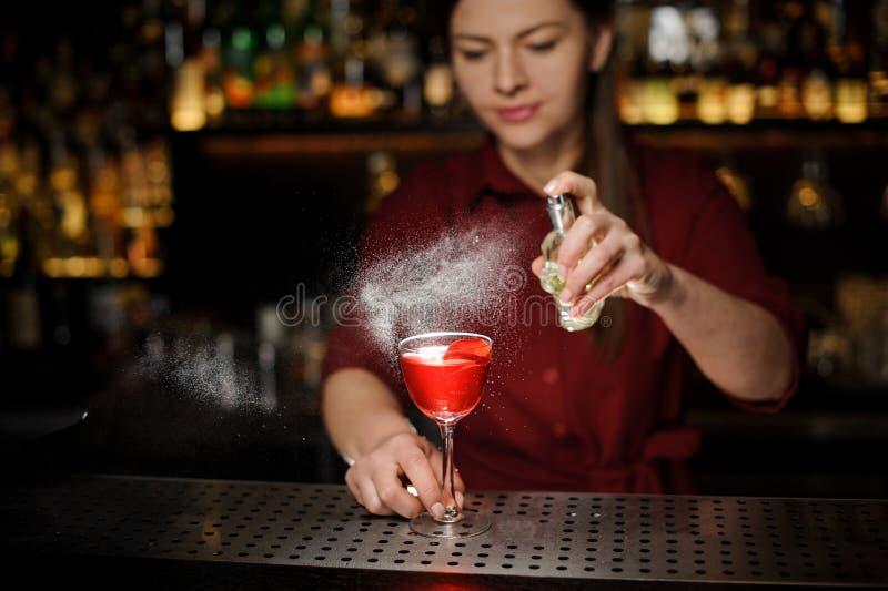 O empregado de bar da jovem mulher que polvilha um vidro de cocktail encheu-se com o cocktail saboroso do verão da seringa de Ape imagens de stock royalty free
