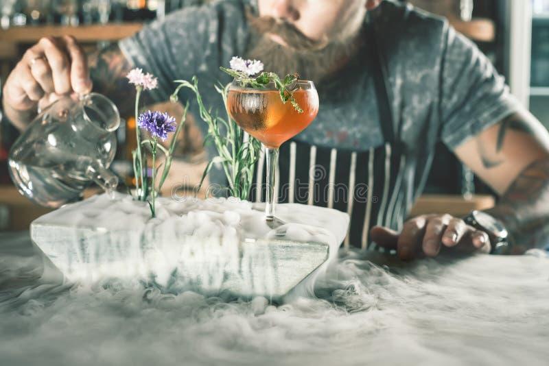 O empregado de bar do close up está fazendo o cocktail com vapor do gelo imagem de stock royalty free