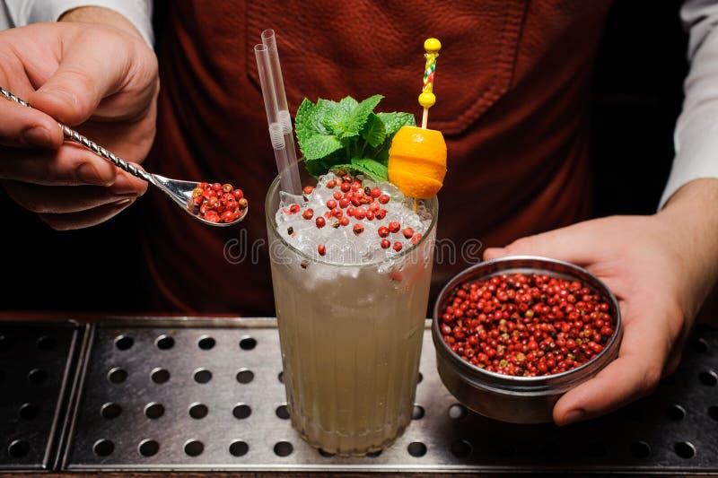 O empregado de bar está decorando o cocktail com pimenta cor-de-rosa imagem de stock