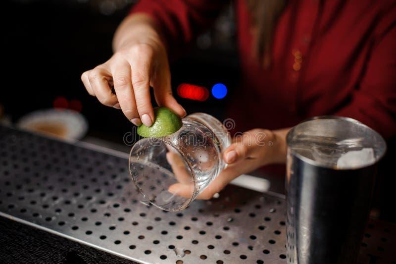 O empregado de bar fêmea entrega a fricção de um vidro com o suco de lima foto de stock