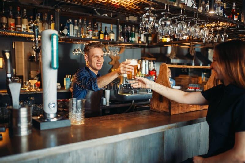 O empregado de bar masculino passa o vidro da cerveja ao visitante fêmea imagens de stock