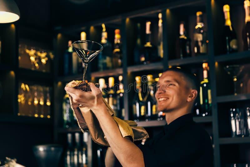 O empregado de bar olha um cristal O barman que limpa o vidro na barra foto de stock