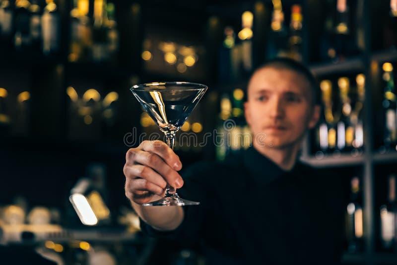 O empregado de bar olha um cristal O barman que limpa o vidro na barra fotos de stock