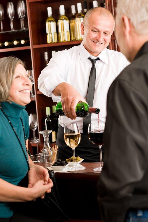 O empregado de bar sênior dos pares da barra de vinho derrama o vidro imagens de stock royalty free