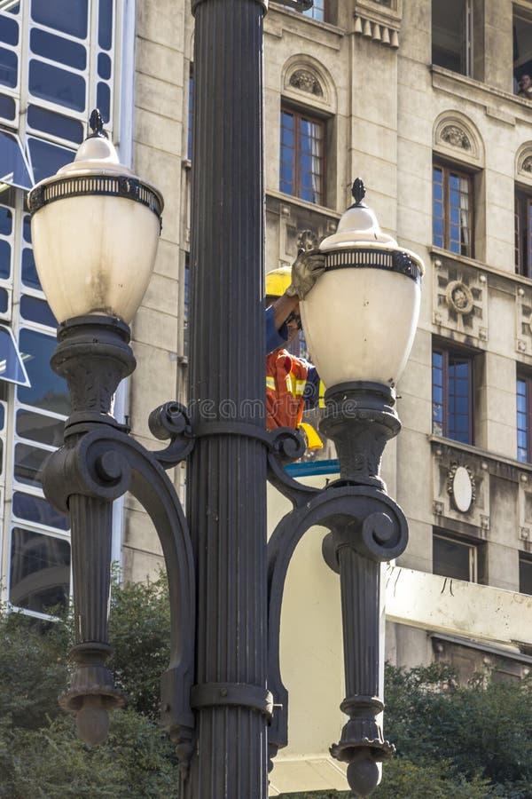 O empregado de Luz Consortium mantém e troca lâmpadas pelos polos velhos foto de stock
