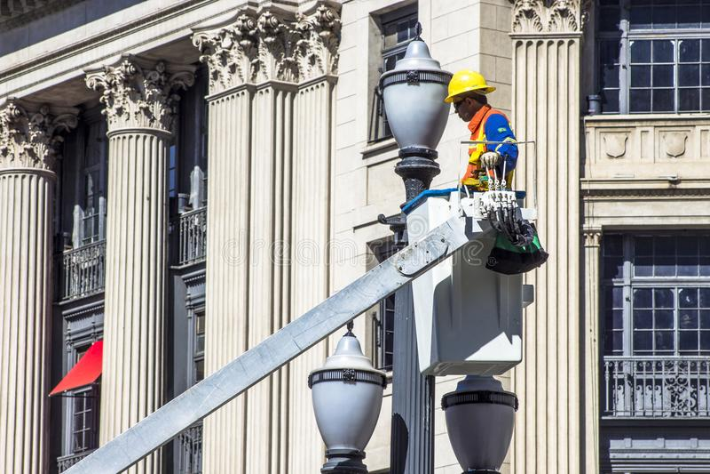 O empregado de Luz Consortium mantém e troca lâmpadas pelos polos velhos imagens de stock