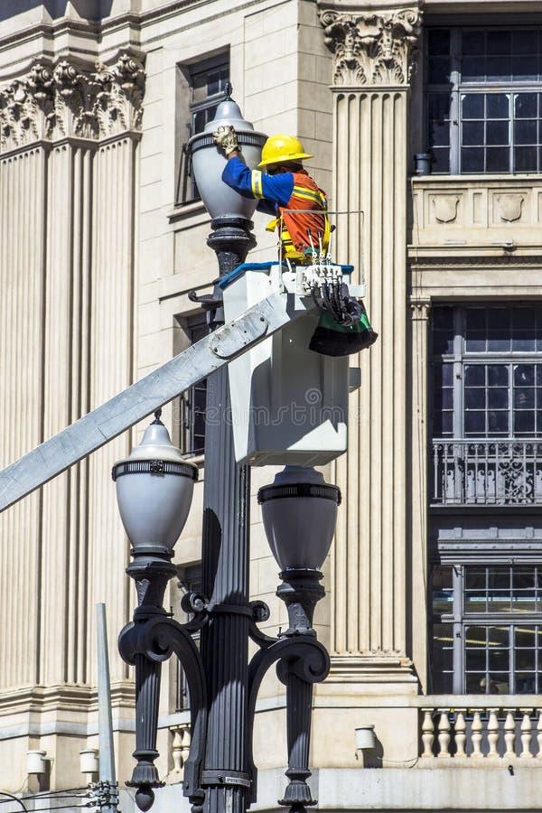 O empregado de Luz Consortium mantém e troca lâmpadas pelos polos velhos fotografia de stock
