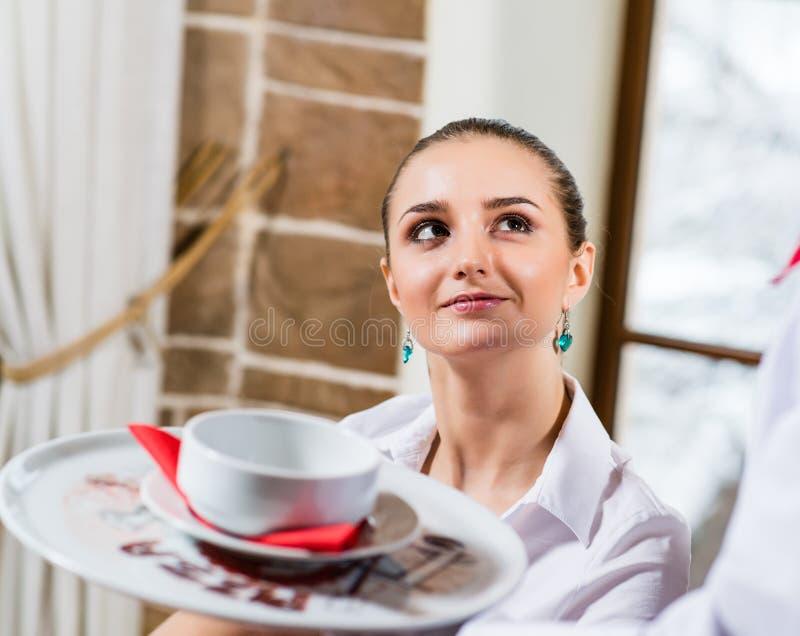 O empregado de mesa traz um prato para uma mulher agradável imagem de stock