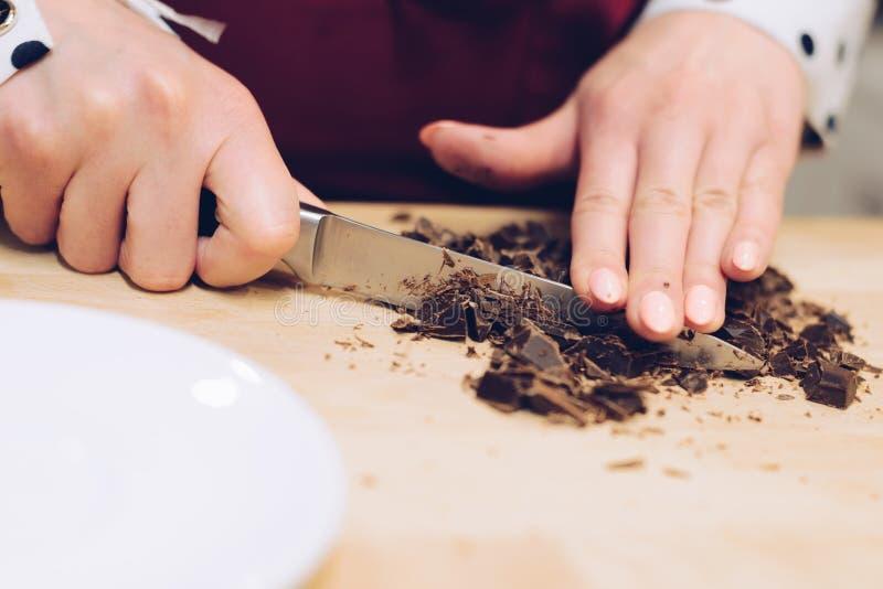 O empregado do café corta o chocolate em partes pequenas foto de stock