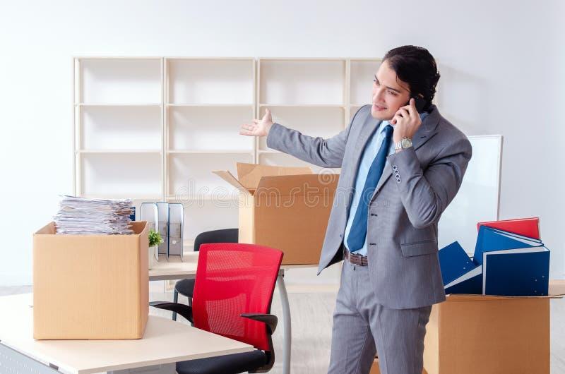 O empregado do homem novo com as caixas no escrit?rio fotos de stock royalty free