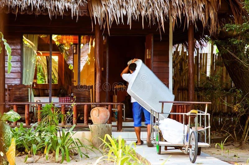 O empregado do hotel leva um colchão novo na sala de hotel Bungalows de limpeza A casa de madeira na selva, o líquido de limpez fotos de stock