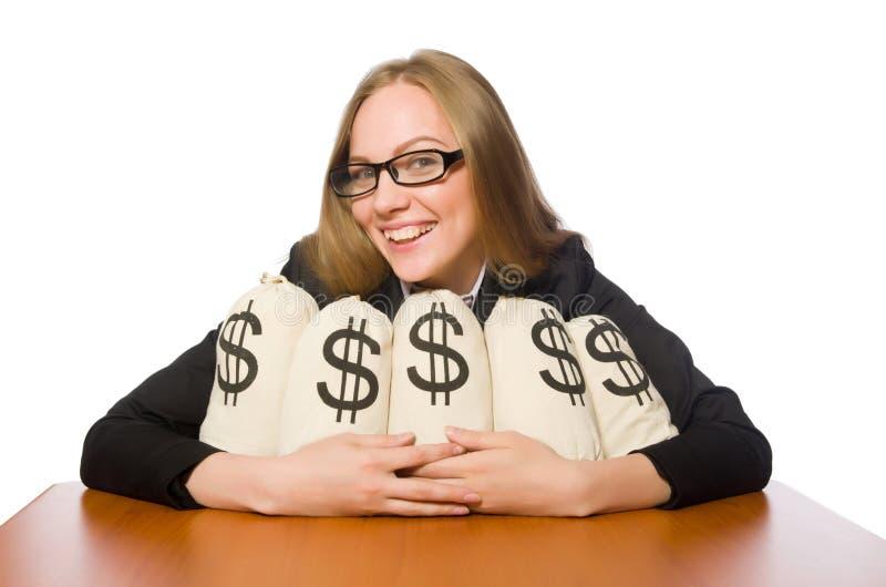 O empregado do sexo feminino com os sacos do dinheiro em sua tabela fotografia de stock royalty free