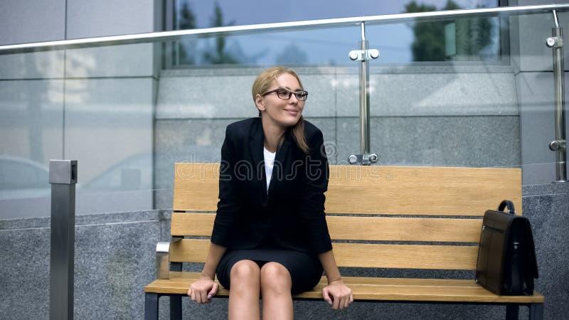 O empregado do sexo feminino do escritório que senta-se no banco, preocupando o ataque incomoda no trabalho, esforço foto de stock